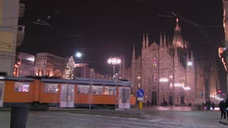 A trolley passes at night on a street in front of the Duomo cathedral in Milan, Italy.