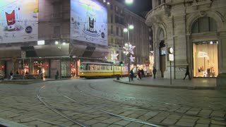 A trolley passes at night on a street in Milan, Italy.