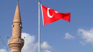 A Turkish flag flies near a mosque.