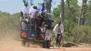 A van crowded with passengers makes its way along a dirt road in East Africa.