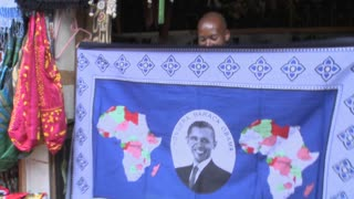 A vendor holds up a blanket with Barack Obama picture on it in kenya.