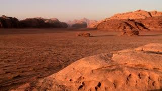 A wide establishing shot of the vast desert sands of Wadi Rum, Jordan.
