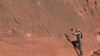 A woman photographs ancient and mysterious petroglyphs depict humans and camels in the Saudi desert near Wadi Rum, Jordan.