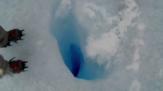 A zoom into a deep blue hole in a glacier.