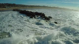 Aerial over a generic California coastline with big waves rolling in and breaking.
