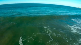 Aerial pan over large tsunami style waves rolling up to a generic beach.