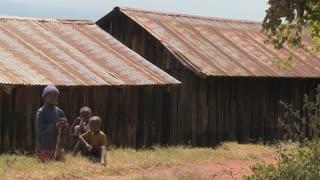 African children sit near a slum.