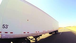 An 18 wheeler truck moves across the desert in this POV shot.