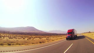 An 18 wheeler truck moves across the desert in this POV shot.