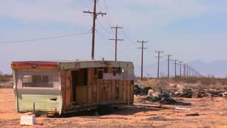An abandoned trailer sits in the middle of the Mojave desert.