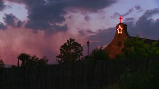 An adobe church at dusk.