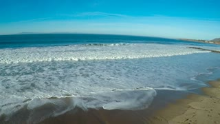 An aerial over a generic beach heading out to the ocean with large waves and surf breaking.