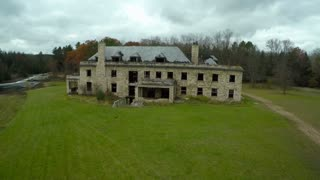 An aerial over a spooky abandoned mansion in the countryside.