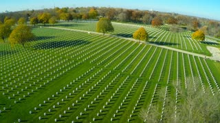 An aerial over a vast cemetery of headstones honors America's veterans.