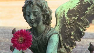 An angel sculpture in a cemetery on a grave.