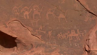 Ancient and mysterious petroglyphs depict humans and camels in the Saudi desert near Wadi Rum, Jordan.