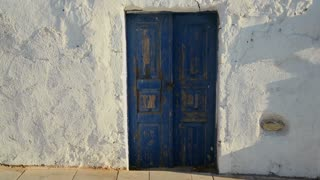 Beautiful whitewashed walls and blue doors on the island of Santorini in Greece.