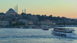 Boats pass in the harbor in front of the mosques of Istanbul, Turkey at dusk.