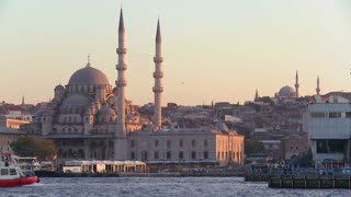Boats passing in front of the mosques of Istanbul, Turkey at dusk.