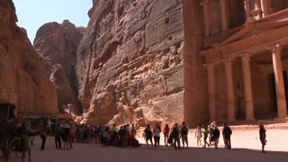Camels and tourists in front of the facade of the Treasury building in the ancient Nabatean ruins of Petra, Jordan.