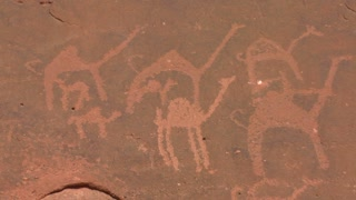 Close up of ancient and mysterious petroglyphs depicting humans and camels in the Saudi desert near Wadi Rum, Jordan.