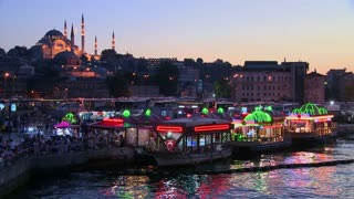 Colorful boats at dusk in front of a mosque in Istanbul, Turkey.