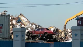 Cranes lift and move scrap metal around abandoned and destroyed cars in a junkyard or scrap metal yard.