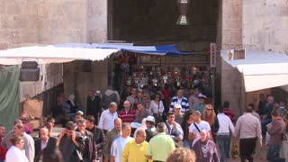 Crowds of people walk near the Damascus Gate in the Arab Quarter of the old city of Jerusalem.
