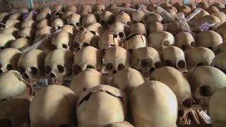 Dolly along hundreds of skulls in rows in a church following the genocide in Rwanda.