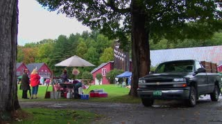 Families picnic near trees and red barns at a Country Fair in Vermont.