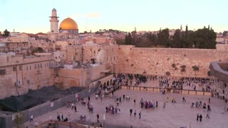 Fast motion of people beneath The Dome of the Rock as it towers over the Old City of Jerusalem and the Wailing Wall.