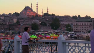 Fisherman and colorful boats at dusk in front of a mosque in Istanbul, Turkey.