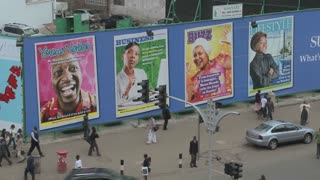 Handprinted billboard signs along a busy street in kenya.