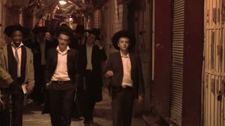 Hassidic Jews walk in the Arab Quarter of the old city of Jerusalem at night.