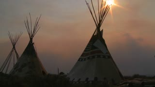 Indian teepees stand in a native american encampment at sunset.