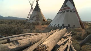 Indian teepees stand in a native american encampment.