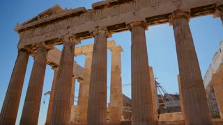 Low angle pan of the columns of the Acropolis and Parthenon on the hilltop in Athens, Greece.
