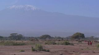 Masai warriors walk in in front of Mt. Kilimanjaro in Tanzania, East Africa.