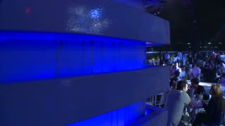 Move along blue wall to reveal hundreds of people partying at a giant open air nightclub.