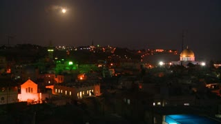 Night over the old city of Jerusalem with the moon rising.