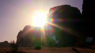 Pan across a sunrise in the desert as a camel train crosses the Saudi desert in Wadi Rum, Jordan.