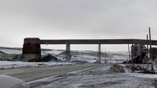 Pan across an old abandoned mine in winter with traffic passing on a road.