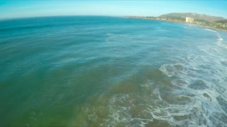 Pan across large waves breaking onto the shore in Ventura, California.