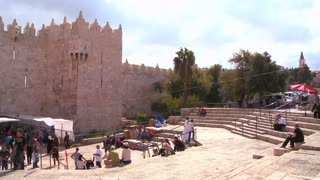 Pan across of people walk out of the Damascus Gate in the old city of Jerusalem.