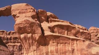 Pan across to an amazing arch formation in the Sadi desert in Wadi Rum, Jordan with a Bedouin man walking through.