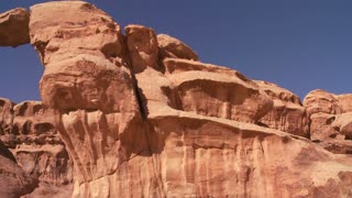 Pan across to an amazing arch formation in the Sadi desert in Wadi Rum, Jordan.