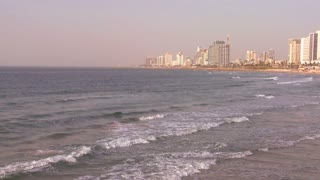 Pan of Tel Aviv, Israel with waves breaking on the shore.