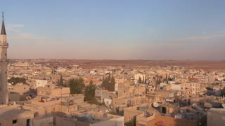 Pan to reveal a mosque towering above the Arab city of Madaba in Jordan.