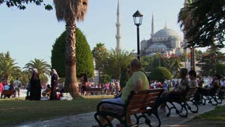 Pedestrians walk and sit on benches near the Blue Mosque in istanbul, Turkey.