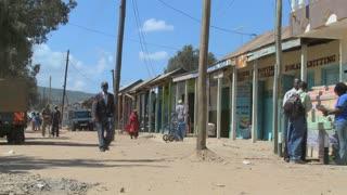 Pedestrians walk on the dirt streets of Maralal in Northern Kenya.